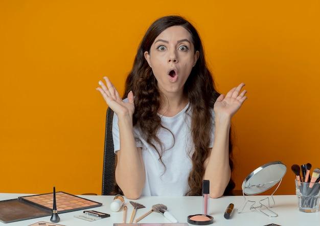 빈 손을 보여주는 메이크업 도구와 메이크업 테이블에 앉아 놀된 젊은 예쁜 여자