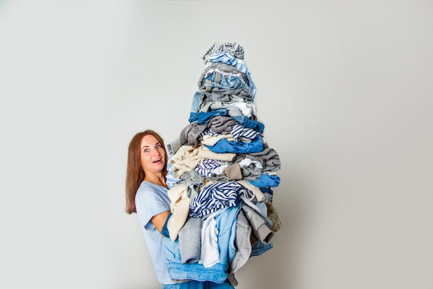 Surprised young red-haired woman carrying pile of cluttered clothes at home.