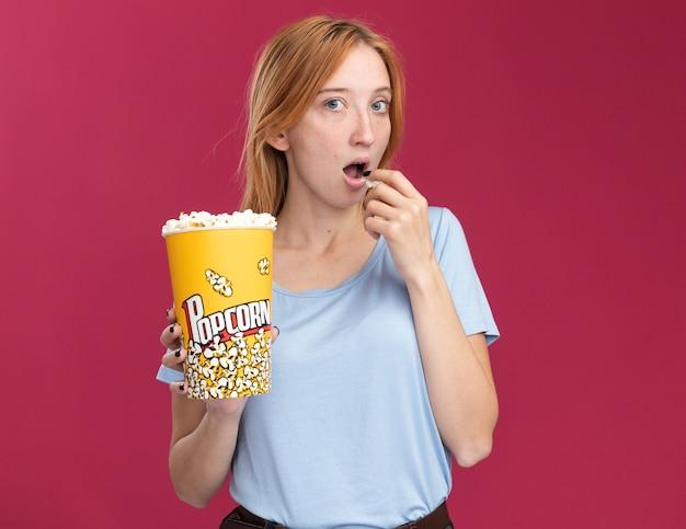 팝콘 양동이를 들고 복사 공간이 있는 분홍색 벽에 격리된 팝콘을 먹는 주근깨가 있는 놀란 어린 빨간 머리 생강 소녀