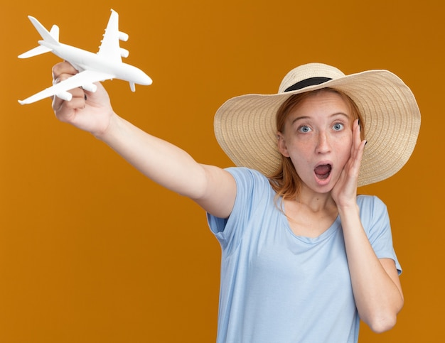 Surprised young redhead ginger girl with freckles wearing beach hat holds model plane isolated on orange wall with copy space