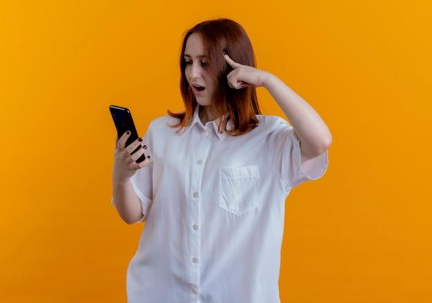 놀란 된 젊은 빨간 머리 소녀 잡고 전화를보고 노란색 배경에 고립 된 머리에 손가락을 넣어