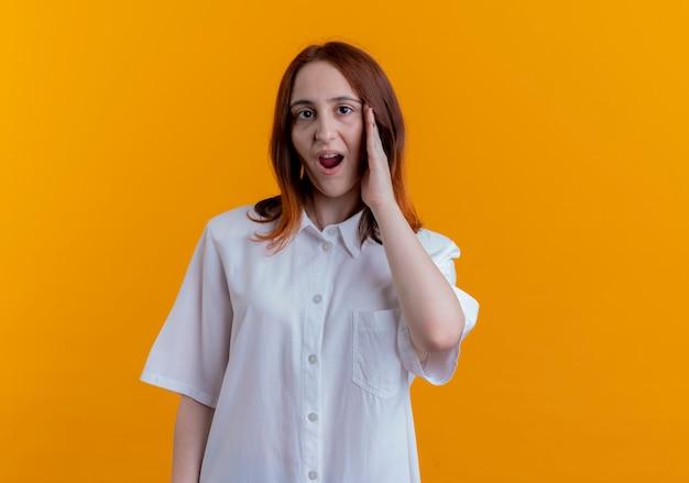 Giovane ragazza sorpresa della testarossa che mette la mano sulla guancia isolata sulla parete gialla