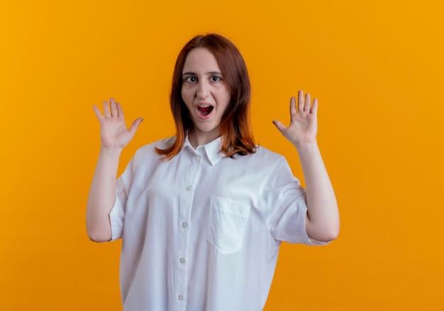 놀란 된 젊은 빨강 머리 소녀 노란색 배경에 고립 된 손을 확산