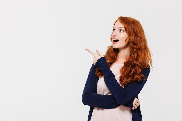 Surprised young redhead lady pointing