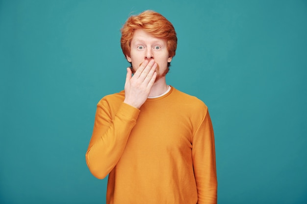 Surprised young redhead man in orange sweater standing on blue and covering mouth in excitement
