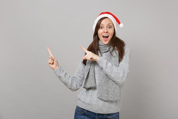 灰色のセーターのスカーフのクリスマスの帽子をかぶった驚いた若いサンタの女の子は、口を大きく開いたまま、灰色の背景で隔離された人差し指を脇に向けます。明けましておめでとうございます2019お祝いホリデーパーティーのコンセプト。