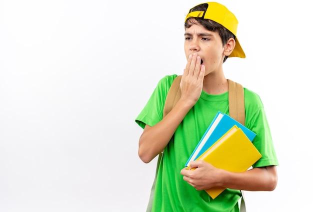 本を保持しているキャップ付きのバックパックを身に着けている驚いた少年は、コピースペースのある白い壁に隔離された手で口を覆った