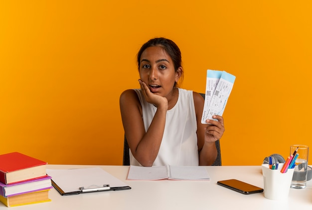 Giovane studentessa sorpresa che si siede allo scrittorio con gli strumenti della scuola che tengono i biglietti e che mettono la mano sul mento isolato sulla parete arancione
