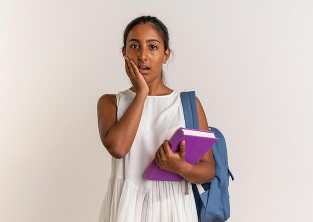 Giovane scolara sorpresa che porta il libro della tenuta della borsa posteriore e che mette la mano sulla guancia su bianco