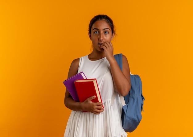 Sorpreso giovane studentessa che indossa la borsa posteriore tenendo i libri e mettendo la mano sulla bocca