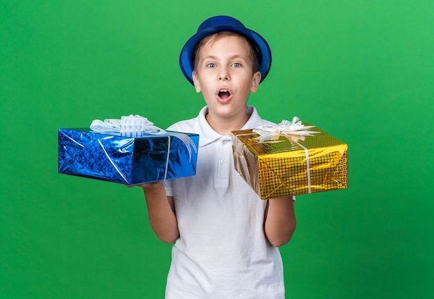 Surprised young slavic boy with blue party hat holding gift box on each hand isolated on green wall with copy space
