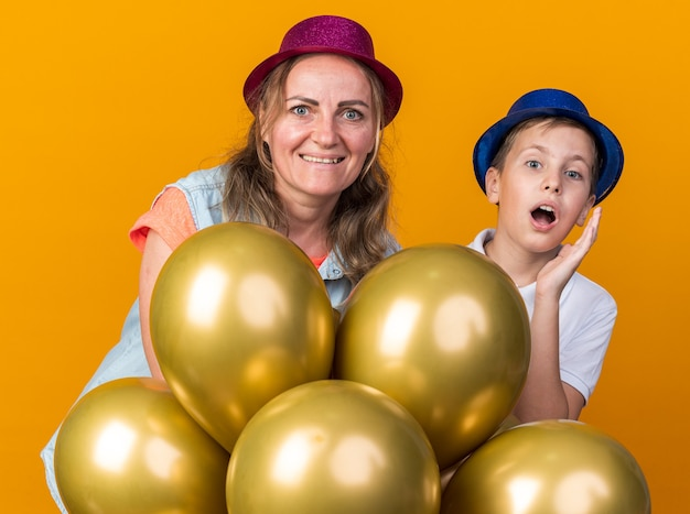 Surprised young slavic boy with blue party hat holding helium balloons with his mother wearing purple party hat isolated on orange wall with copy space