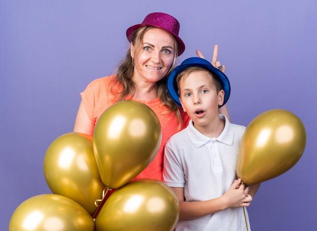 Sorpreso giovane ragazzo slavo con cappello da festa blu che tiene palloncini di elio con sua madre che indossa cappello da festa viola isolato sul muro viola con spazio di copia
