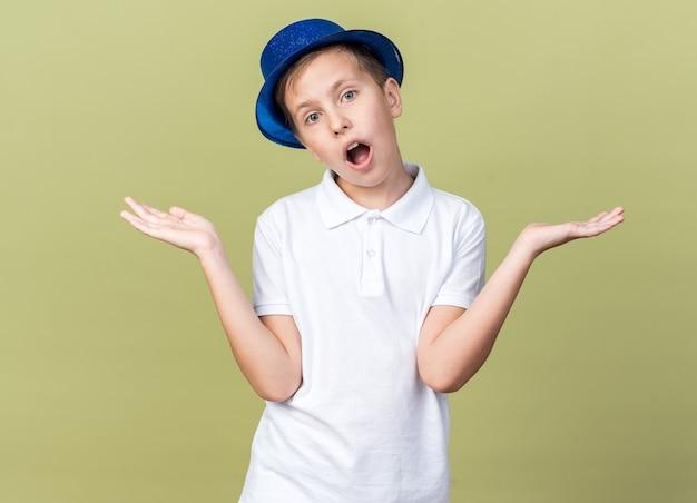 Удивленный молодой славянский мальчик в синей праздничной шляпе, держа руки открытыми, изолирован на оливково-зеленой стене с копией пространства