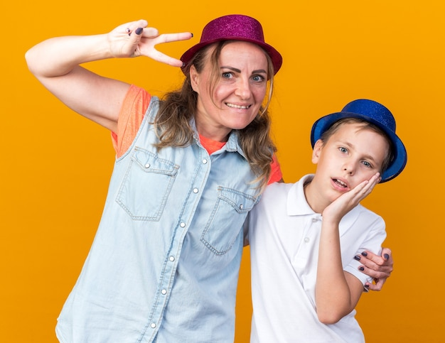 Surprised young slavic boy with blue party hat putting hand on face and standing with his mother wearing purple party hat gesturing victory sign isolated on orange wall with copy space