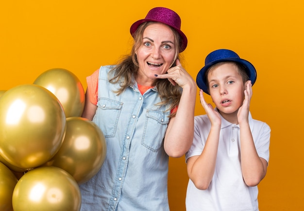 Surprised young slavic boy with blue party hat standing raising hands up with his mother wearing purple party hat holding helium balloons isolated on orange wall with copy space