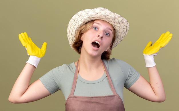 Giovane giardiniere femminile slavo sorpreso che indossa cappello e guanti da giardinaggio che tengono le mani aperte isolate sulla parete verde oliva con lo spazio della copia