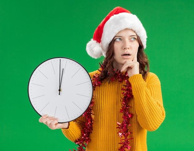 Удивленная молодая славянская девушка в новогодней шапке и с гирляндой на шее кладет палец на лицо и держит часы, глядя в сторону