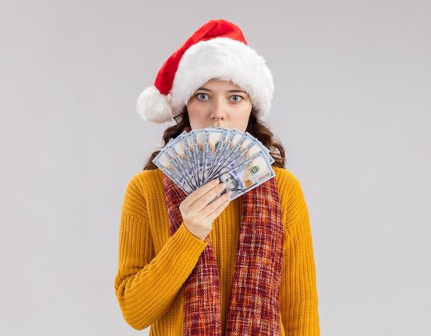 サンタの帽子とコピースペースで白い壁に隔離されたお金を保持している首の周りのスカーフで驚いた若いスラブの女の子