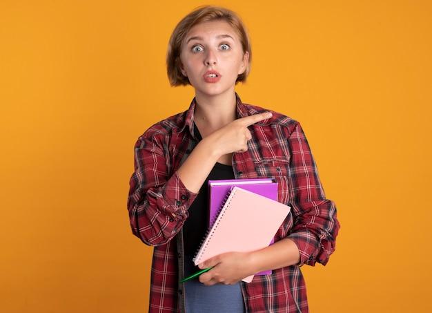 La giovane studentessa slava sorpresa tiene il libro della penna e i punti del taccuino a lato
