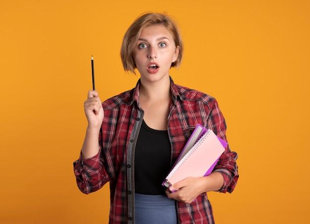 La giovane studentessa slava sorpresa tiene il libro di matita e il taccuino