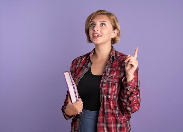 La giovane studentessa slava sorpresa indica con le mani il libro e il taccuino