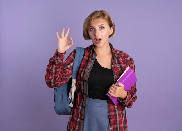 배낭을 입고 놀란 된 젊은 슬라브 학생 소녀 보유 책 및 노트북 제스처 확인 손 기호