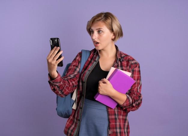 バックパックを着て驚いた若いスラブ学生の女の子が本を持ち、ノートが電話を見る