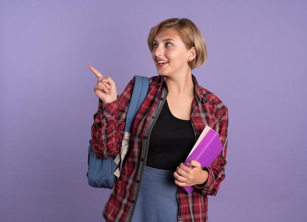 La giovane studentessa slava sorpresa che indossa lo zaino tiene il libro e il taccuino che guardano e che indicano