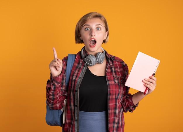 La giovane studentessa slava sorpresa con le cuffie che indossa lo zaino tiene il taccuino e la penna punta in alto