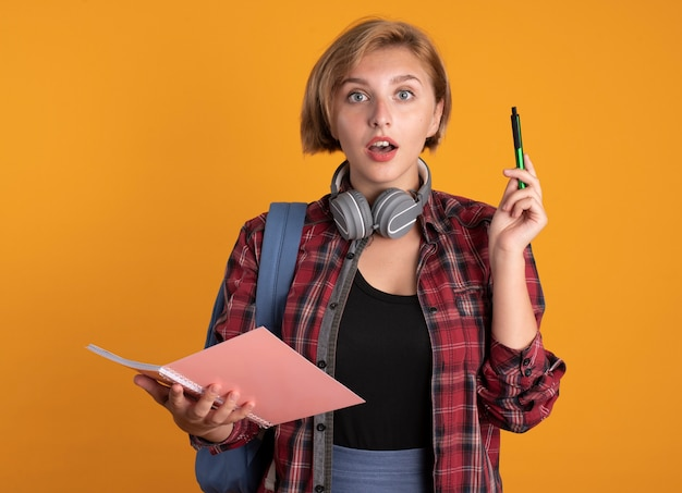 La giovane studentessa slava sorpresa con le cuffie che indossa lo zaino tiene la penna e il taccuino