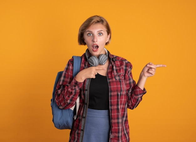 Удивленная молодая славянская студентка с наушниками в рюкзаке указывает на бок двумя руками