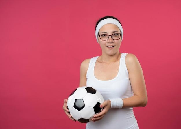 ヘッドバンドを身に着けている光学メガネで驚いた若いスポーティな女の子