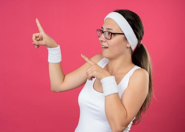 Sorpresa giovane ragazza sportiva in occhiali ottici che indossa fascia e braccialetti punta verso l'alto e guarda di lato