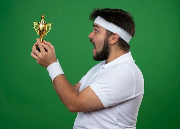 Giovane uomo sportivo sorpreso in piedi nella vista di profilo che indossa la fascia e il braccialetto che tiene e che esamina la tazza del vincitore isolata sulla parete verde