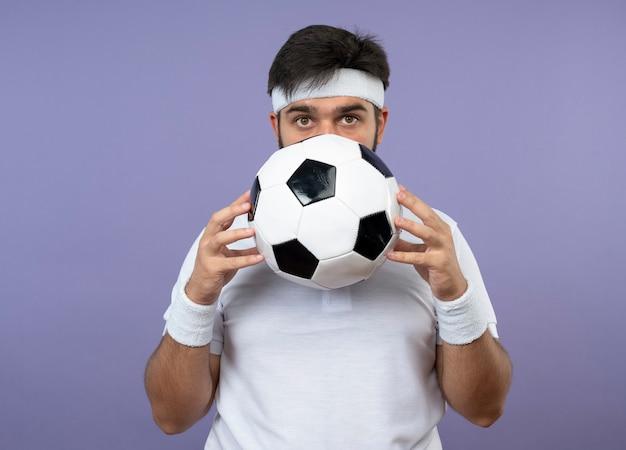Удивленный молодой спортивный мужчина с головной повязкой и браслетом закрыл лицо мячом