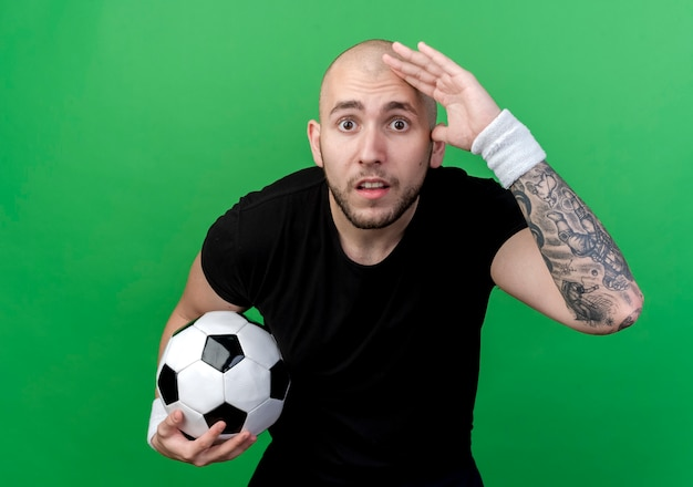 Surprised young sporty man wearing wristband holding ball and looking at distance with hand isolated on green