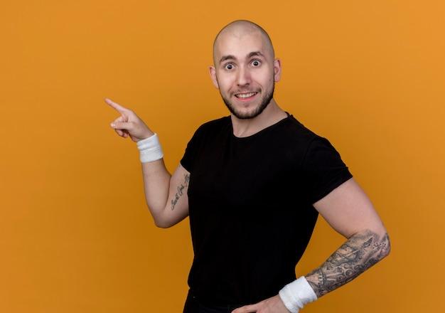 Il giovane sportivo sorpreso che indossa il braccialetto indica a lato e che mette la mano sull'anca isolata sulla parete arancione con lo spazio della copia