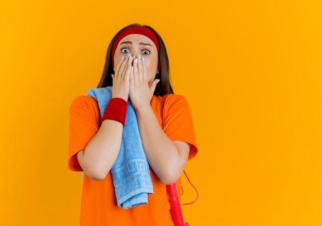 コピースペースのあるオレンジ色の壁に手を離して、肩にタオルと縄跳びのヘッドバンドとリストバンドを身に着けている驚いた若いスポーティな女性