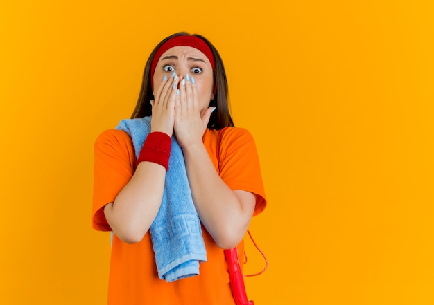 Surprised young sporty woman wearing headband and wristbands with towel and jump rope on shoulders  keeping hands on mouth isolated on orange wall with copy space
