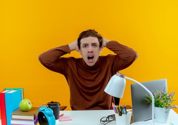 学校の道具を持って机に座っている驚いた若い学生の男の子は黄色に頭をつかんだ