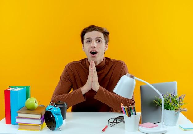 Удивленный молодой студент мальчик сидит за столом со школьными инструментами, показывая жест молитвы, изолированный на желтой стене