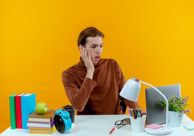 학교 도구로 책상에 앉아 놀란 젊은 학생 소년 노트북을 사용하고 노란색에 뺨에 손을 넣어