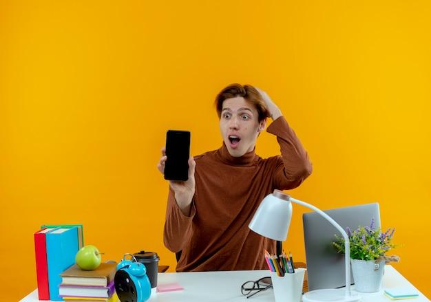 Ragazzo giovane studente sorpreso che si siede allo scrittorio con gli strumenti della scuola che tengono e che esaminano il telefono che mette la mano sulla testa isolata sulla parete gialla