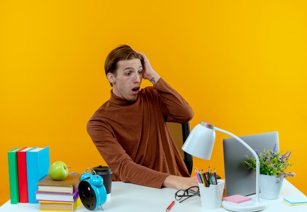 Il giovane ragazzo sorpreso dell'allievo che si siede allo scrittorio con gli strumenti della scuola ha utilizzato il computer portatile e che mette la mano sulla testa sul giallo