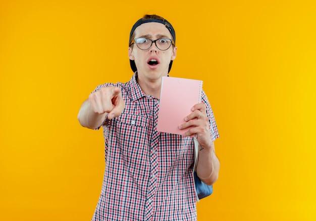 バックバッグとメガネとノートを保持し、白い壁に分離されたジェスチャーを示すキャップを身に着けている驚いた若い学生の男の子