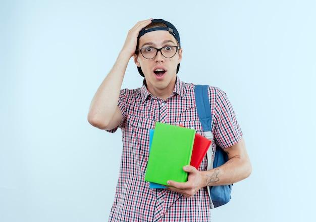 Ragazzo giovane sorpreso dell'allievo che indossa la borsa posteriore e gli occhiali e il berretto che tengono i libri e che mette la mano sulla testa su bianco