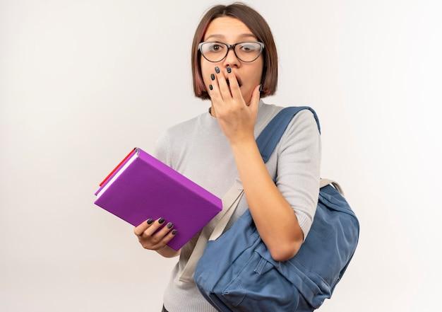 Удивленная молодая студентка в очках и задней сумке, держащая книги, положив руку на рот, изолированную на белой стене