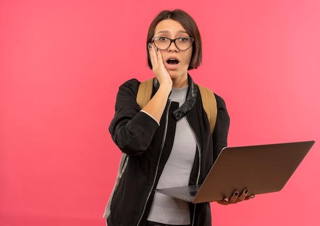 Ragazza giovane studentessa sorpresa con gli occhiali e borsa posteriore che tiene il computer portatile mettendo la mano sul viso isolato sulla parete rosa
