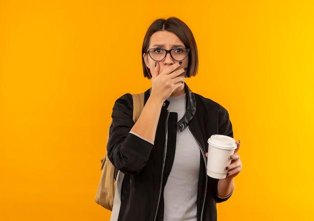 Ragazza giovane studentessa sorpresa con gli occhiali e borsa posteriore che tiene la tazza di caffè di plastica che mette la mano sulla bocca isolata sulla parete arancio